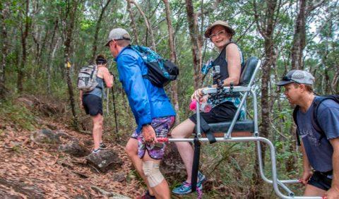 Mulher sentada em uma cadeira especial, carregada por dois rapazes, um na frente e outro atrás, no meio de uma floresta. À esquerda, outra pessoa segue na frente.