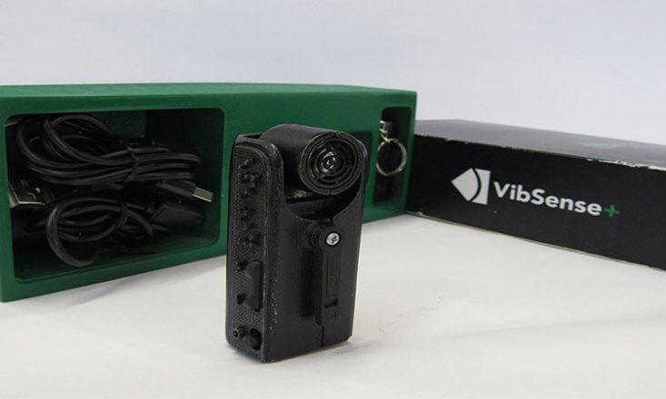 Foto de um equipamento preto, cilíndrico, em primeiro plano, e a caixa dele no fundo da imagem.