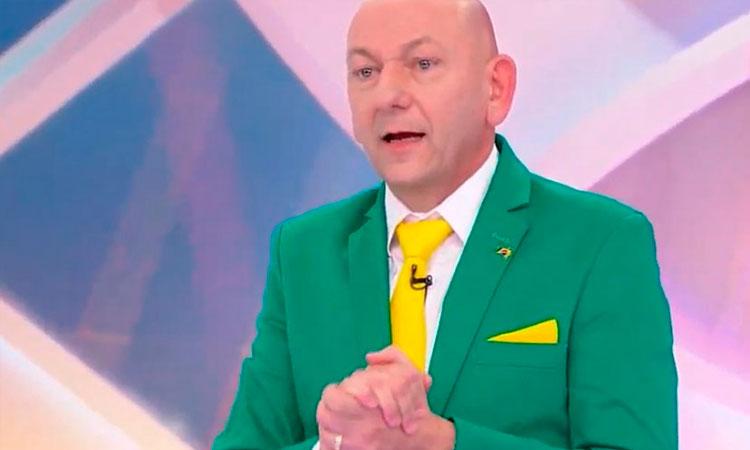 Homem de meia idade, careca, com as mãos postas, vestindo um paletó verde, gravata e lenço de lapela amarelos e um microfone na gravata. Ao fundo, uma tela de várias cores, como rosa, roxo e azul.