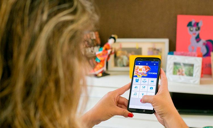 Mulher acessa um aplicativo em seu celular.