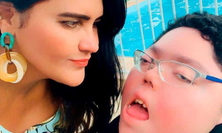 Foto horizontal de uma mulher, à esquerda, olhando para seu filho adolescente, em uma cadeira de rodas. Ao fundo, uma piscina.