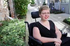 Foto de uma mulher em uma cadeira de rodas, sorrindo, de óculos, cabelos curtos aloirados e uma blusa preta.