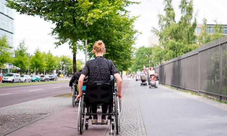 Mulher em cadeira de rodas, de costas, segue por uma rua. A sua frente, outro cadeirante. Ao fundo, algumas pessoas caminham na direção oposta. Do lado esquerdo da imagem, vários carros estacionados.