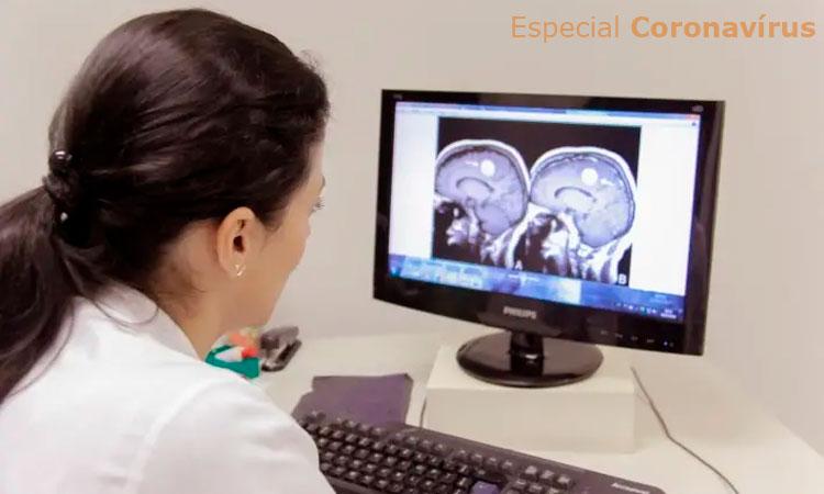 No ambulatório do Instituto Jô Clemente, em São Paulo, uma mulher de costas para a câmera veste um jaleco branco. Ela olha para a tela de um computador onde está projetada a imagem de um exame cerebral.