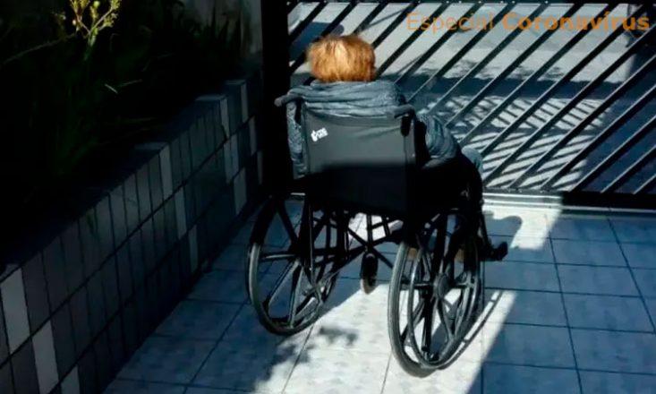 Idosa em uma cadeira de rodas está de costas para a câmera na área externa de um edifício, ao lado de um jardim, tomando sol.