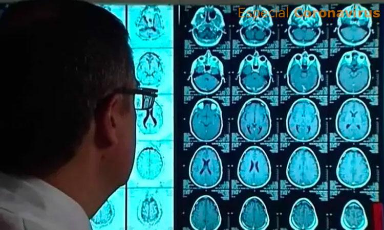 Homem de óculos e roupa branca está de costas para a câmera e olha para a tela de um computador onde estão projetadas imagens de um exame cerebral.