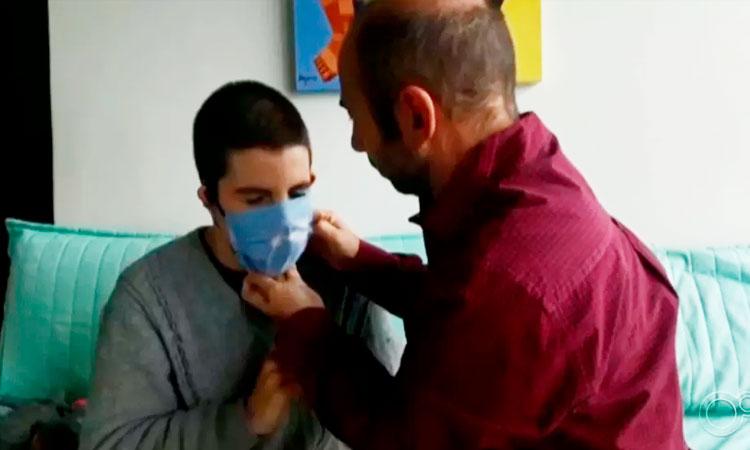 Pai (à direita), de camisa vermelha de mangas compridas, tenta colocar uma máscara azul no filho adolescente, autista, sentado em um sofá esverdeado.