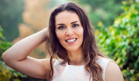 Imagem em foco de uma mulher jovem, bonita, sorrindo, ajeitando os cabelos esvoaçantes. Ao fundo, muitas plantas.
