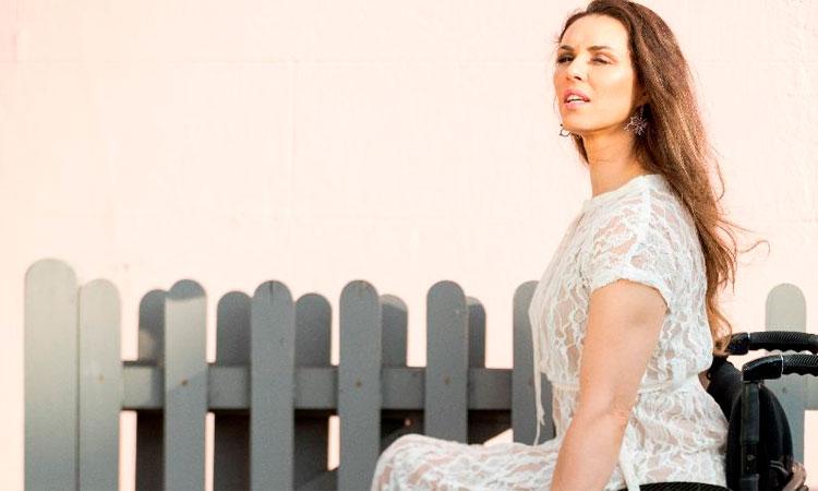 Foto em perfil de uma mulher cadeirante, de olhos fechados, em um vestido branco. Ao fundo, uma cerca cinza.