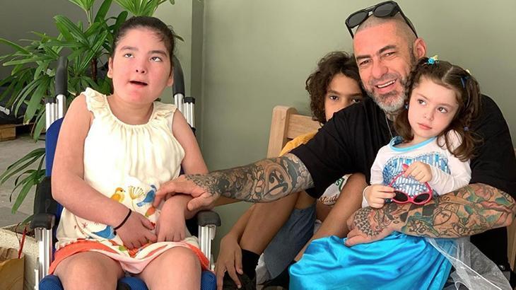 Foto horizontal de quatro pessoas. À esquerda, uma garotinha em uma cadeira de rodas; no centro, meio escondido atrás do homem adulto, um menino; ao lado dele, o pai, com o braço direito tatuado segurando a mãe da filha na cadeira de rodas; e, no colo do homem, uma menininha de vestido azul e branco.