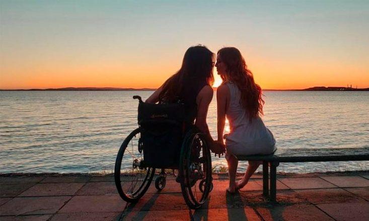Casal de costas, de mãos dadas, com seus rostos bem próximos, como se fossem se beijar na boca. À esquerda a pessoa está sentada em uma cadeira de rodas; à direita, sua parceira está em um banco. Ao fundo, o mar e o sol se pondo.