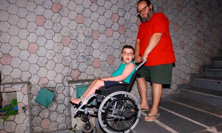 Pai desce uma escada empurrando a cadeira de rodas do filho.