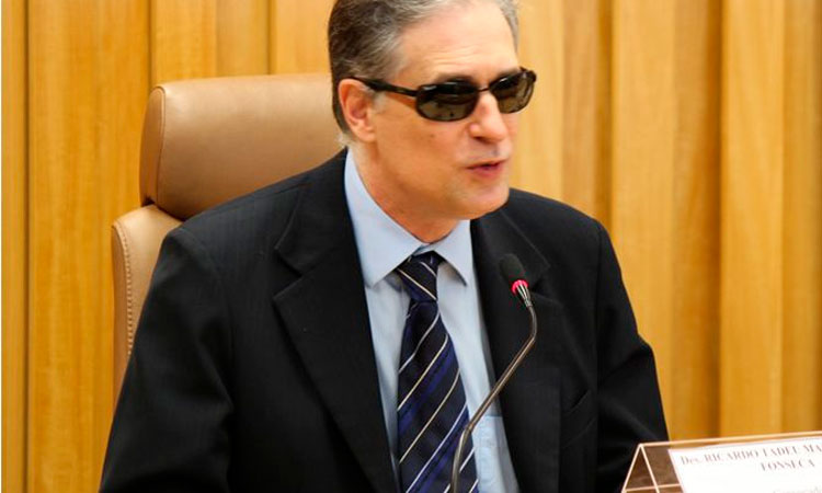 Homem cego, de óculos escuros e paletó preto, está sentado, discursando na frente de um microfone.