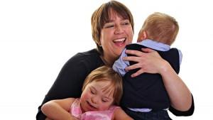 Mãe abraçada com seus dois filhos com down