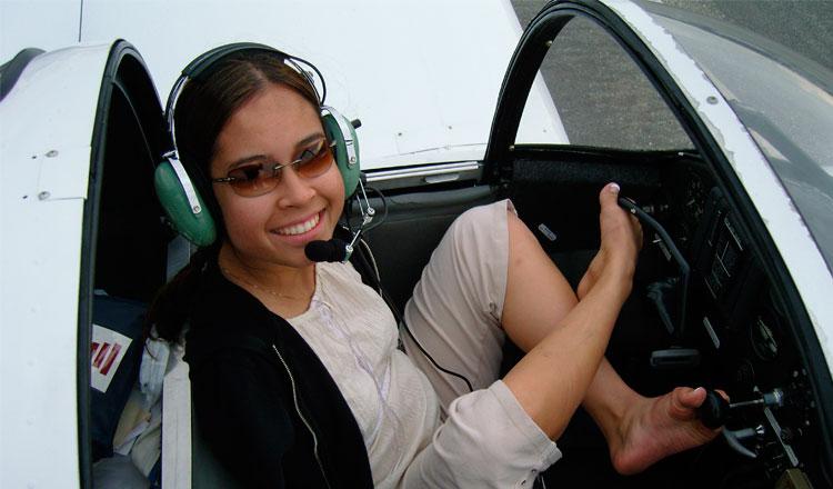 Moça sem braços sorri no cockipit de um avião