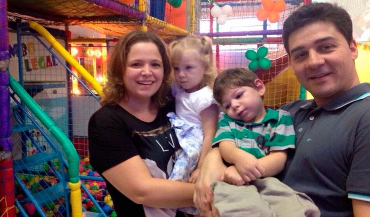 Marina com a filha Maria Rita no colo e o marido Márcio com o filho Gabriel no colo