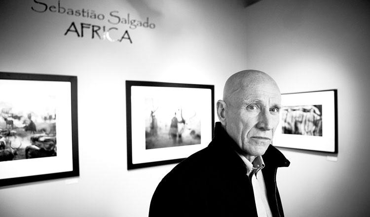 Sebastião Salgado posa com algumas de suas fotos