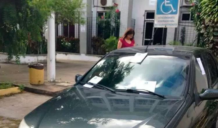 Carro com várias multas e uma mulher ao fundo