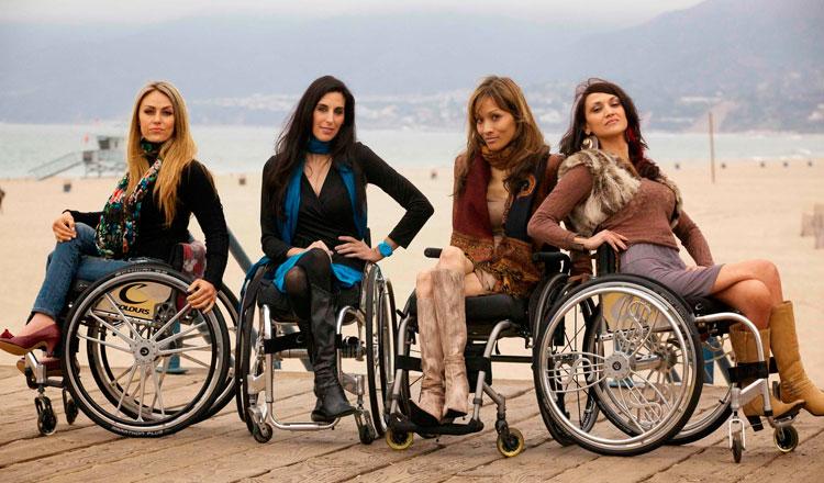 Quatro mulheres em cadeiras de rodas na praia