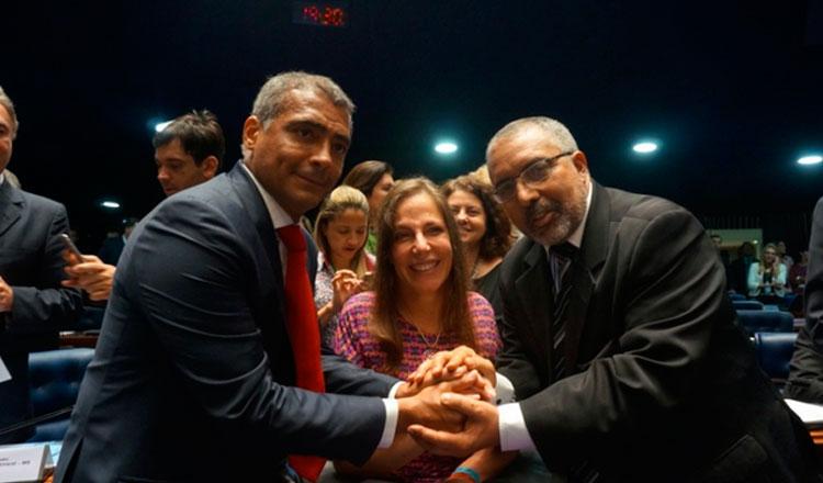 Romário, Mara Gabrilli e Paulo Paim se dão as mãos e sorriem para a câmera