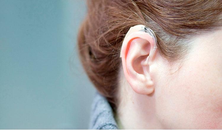 Mulher com aparelho de audição no ouvido direito