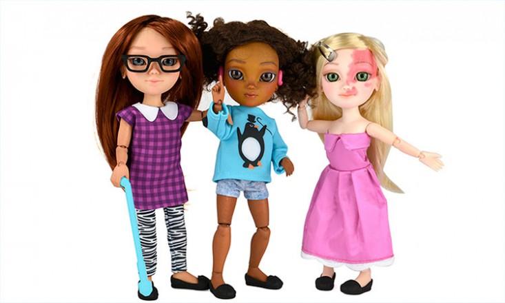 Boneca com bengala ao lado de outra boneca com aparelho auditivo e uma terceira com uma marca de nascença no rosto