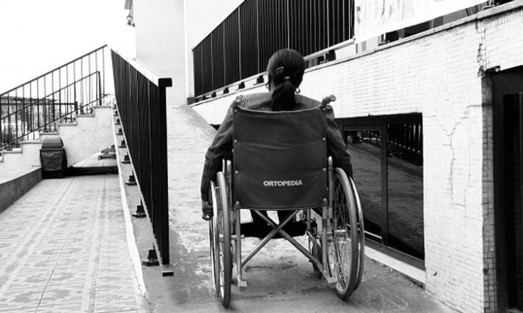 Foto em preto e branco mostra moça em uma cadeira de rodas subindo uma rampa