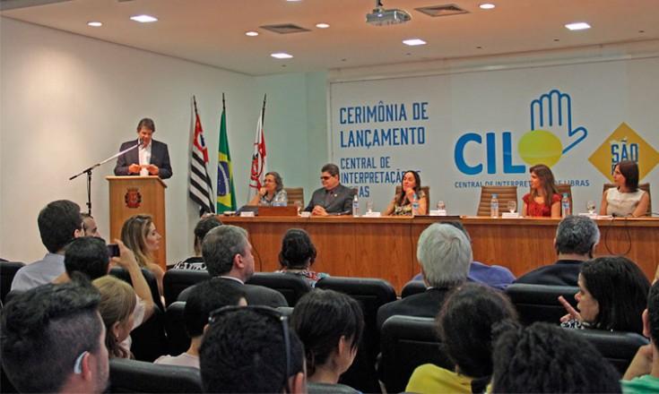 Em um auditório, o Prefeito de São Paulo Fernando Haddad ao microfone, jornalistas sentados a sua frente e quatro mulheres e um homem em uma grande mesa com um painel ao fundo