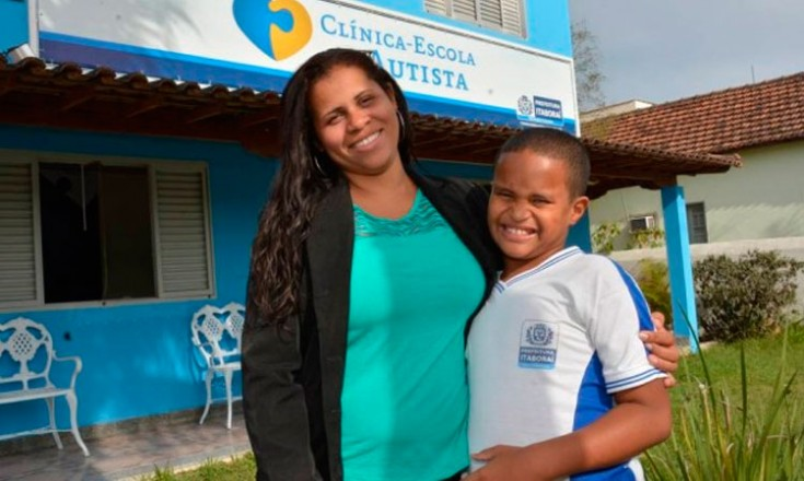 Mulher negra abraçada a um garoto negro fardado, em frente à Clínica-Escola Autista