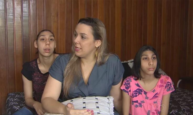 Três mulheres, mãe ao centro e suas filhas uma de cada lado