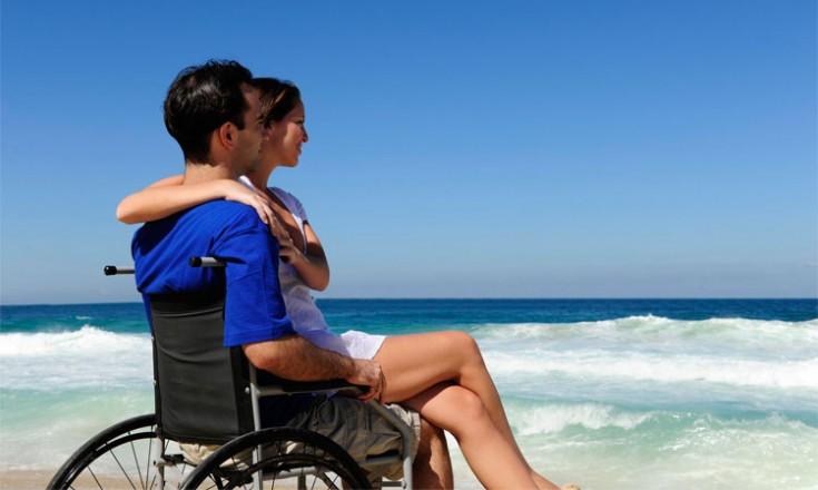 Homem em cadeira de rodas com uma jovem sentada em seu colo observam o mar