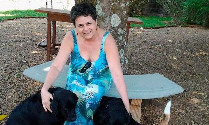 Mulher com um vestido estampado, sentada em um banco de jardim, brincando com dois cachorros