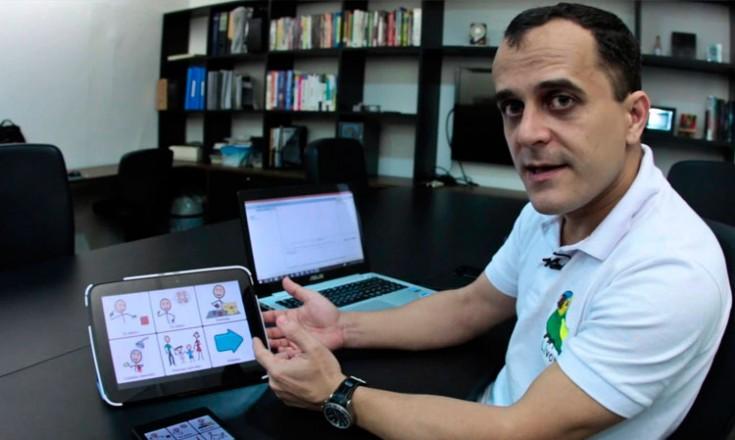 Homem em um escritório, sentado em uma mesa, com um tablet e um notebook a sua frente. No fundo, uma estante com vários livros
