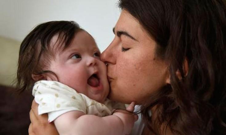 Mulher beija a bochecha de um bebê