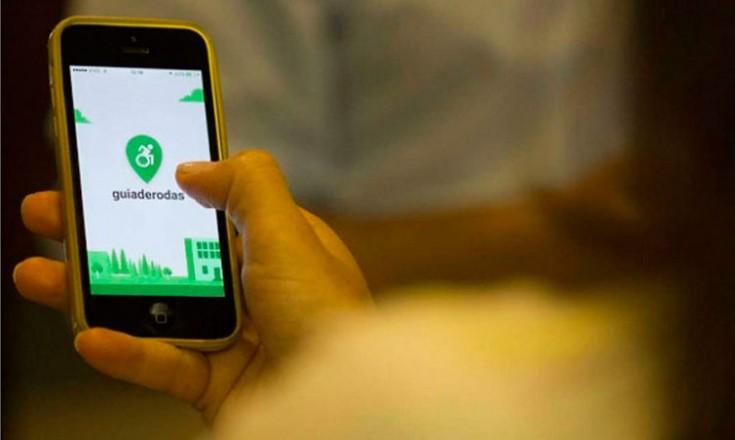 Uma mão segurando um telefone celular com a imagem de entrada do aplicativo Guia de Rodas