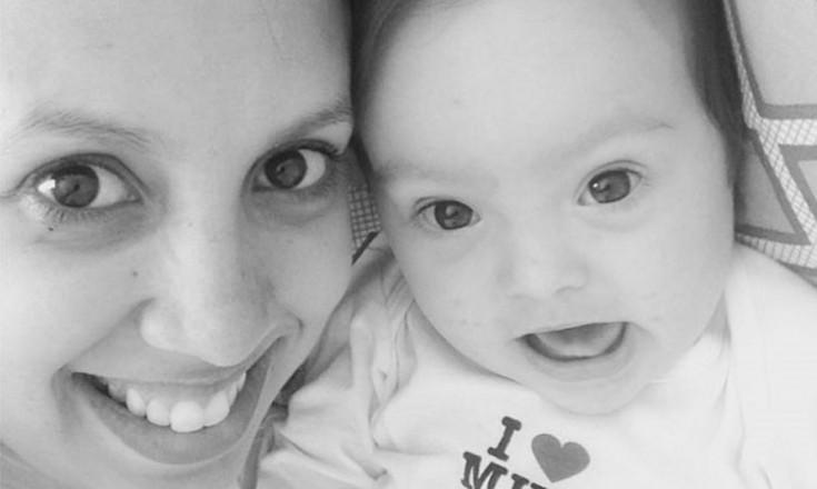Foto em preto e branco, focando bem próximo dos rostos de uma mulher e um bebê com Síndrome de Down. Na roupinha da criança, está escrito I Love Mum