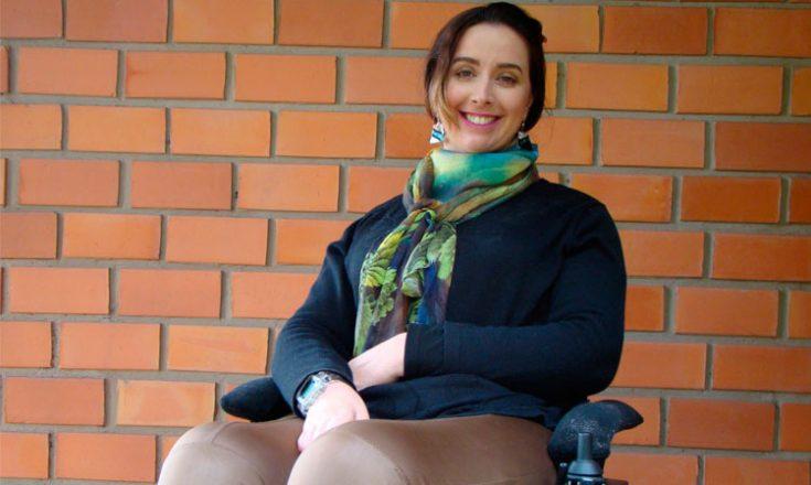 Mulher jovem sentada em uma cadeira de rodas, sorrindo, a frente de uma parede de tijolos horizontais vermelhos