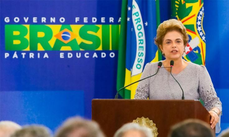 Dilma Rousseff discursando em primeiro plano. Ao fundo, a bandeira do Brasil e a logo do Governo Federal