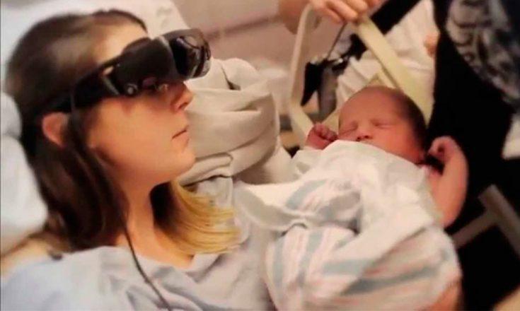 Mulher deitada em uma cama, usando um óculos especiais para cegos, segurando seu bebê recém-nascido no colo