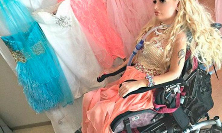 Garota em uma cadeira de rodas e um tubo respiratório na traquéia, vestida e maquiada como a boneca Barbie e, ao lado, vários vestidos