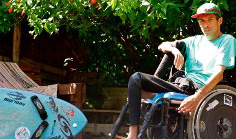 Rapaz em uma cadeira de rodas em frente a uma prancha de surf