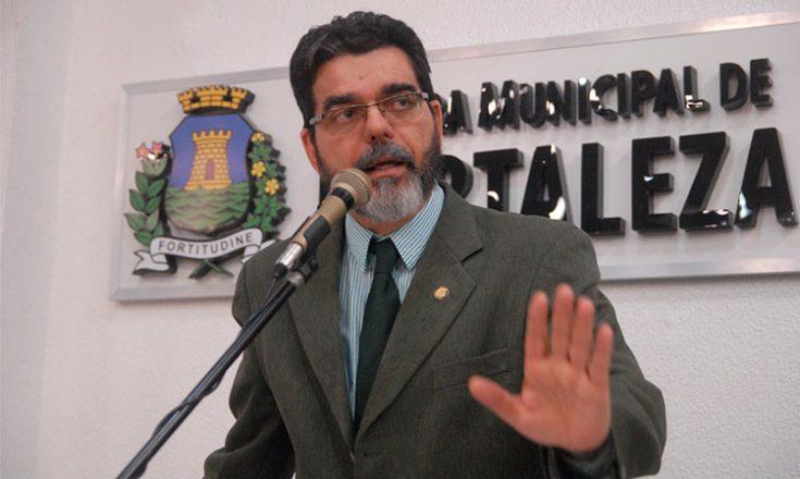 Homem de barba grisalha, óculos e usando paletó e gravata discursa ao microfone à frente de uma placa dizendo Câmara Municipal de Fortaleza