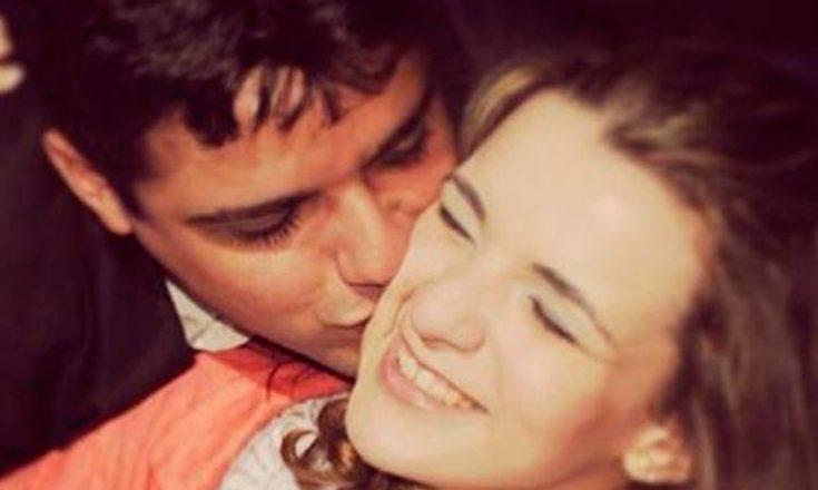 Foto de um jovem casal, em que o rapaz beija o rosto da namorada