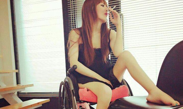 Mulher em uma cadeira de rodas, fumando e com a perna em uma almofada