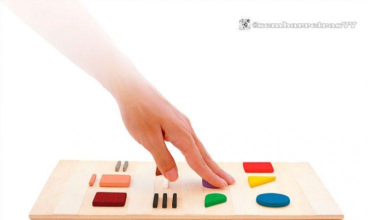 Tábua com os objetos geométricos, em alto relevo, representando as cores, e uma mão passeando sobre eles