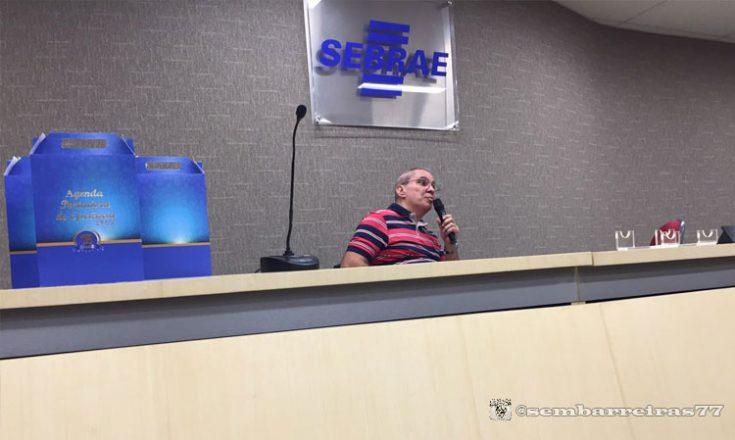 Homem de meia idade ao centro, com um microfone na mão, ladeado por caixas azuis e mais microfones. Embaixo, uma bancada horizontal grande e, em cima, uma placa em acrílico com a palavra Sebrae, letras azuis