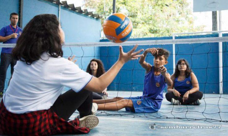 Uma quadra de vôlei sentado. No canto mais próximo da foto, uma professora de costas joga a bola por cima da rede. No fundo, duas crianças e uma mulher, todos sentados, aguardam a bola. Em pé, do lado esquerdo, um homem observa.