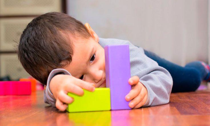 Garotinho deitado de bruços, brincando com dois bloquinhos coloridos, um amarelo e outro azul