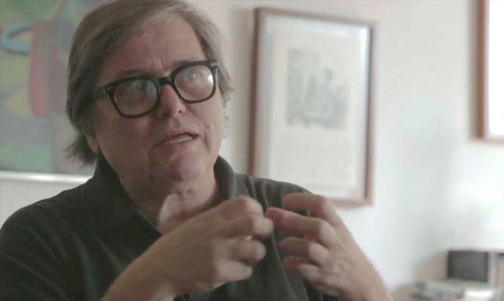 Homem de meia idade, de frente, usando óculos, com suas mãos erguidas. Atrás, dois quadros pendurados à parede