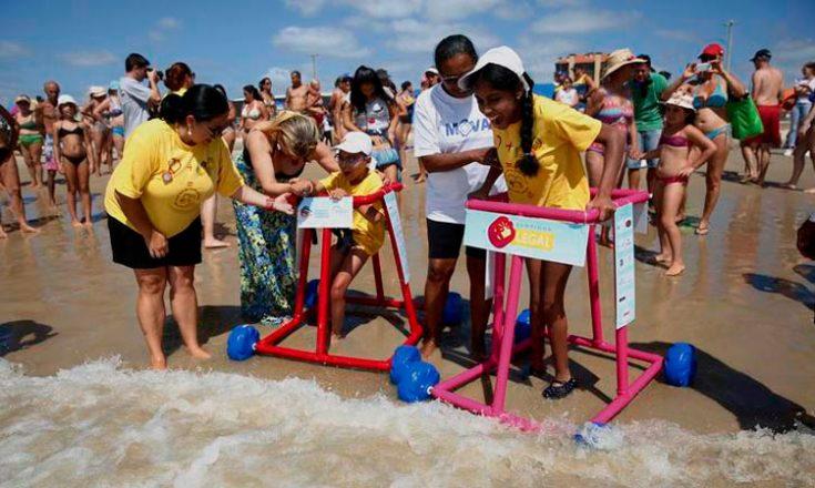 Foto tirada em uma praia em que três adultos ajudam duas crianças a entrar no mar, usando andadores feitos com tubos de PVC. Ao fundo, diversas pessoas em roupas de banho